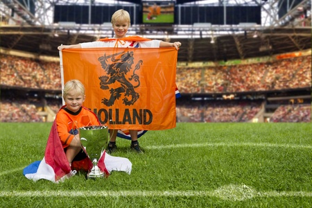 Two young boys in the middle of a huge stadium with Dutch flags and a big trophy,  photo