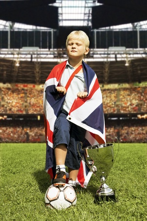 Young boy, posing arrogantly with a British flag, a large trophy and a soccer ball in the center of a huge stadium photo