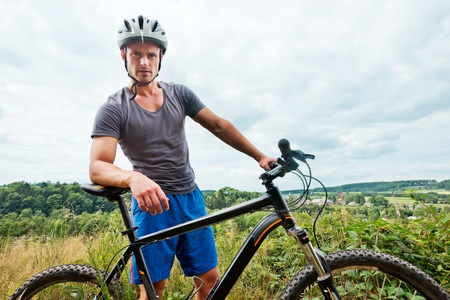cycling helmet: Portrait of a young man with a mountain bike in grassy landscape Stock Photo