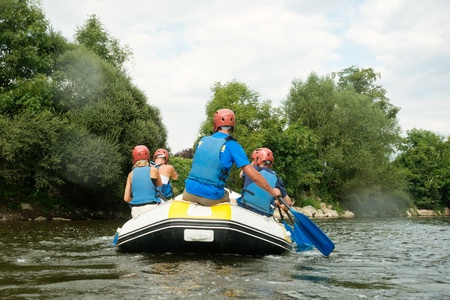 non urban: A group of friends in an inflatable raft moving down a river Stock Photo