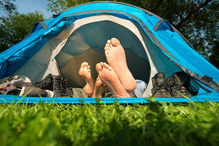 Pieds d'un jeune couple allongé dans une tente