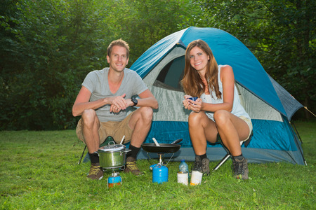 A young couple cooking in front of a tent Stock Photo