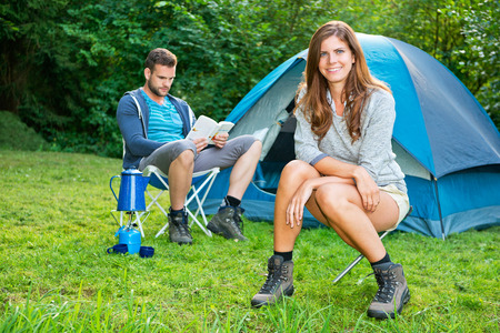 A young couple relaxing in front of a tent photo