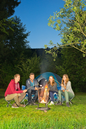 A group of friends sitting around a campfire in front of a tent photo