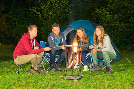 A group of friends sitting around a campfire in front of a tent