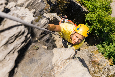 recreational climbing: High angle portrait of young man climbing rock Stock Photo