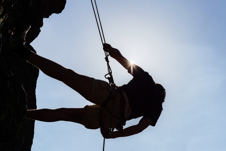 Low angle view of silhouetted man climbing rock against sky Standard-Bild