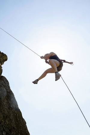 rappelling: Low angle view of female rock climber rappelling against sky