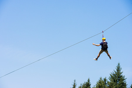 horizontal line: Rear view of young man riding on zip line against blue sky Stock Photo