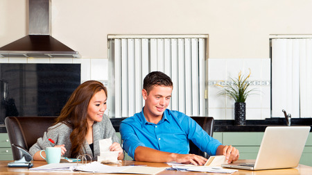 mortage: Young couple at the kitchen table, going over their expences, loans, financial situation and mortage statements