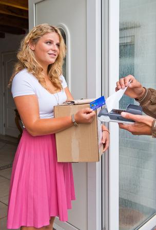 Jeune femme au foyer acceptant une caisse sur l'emballage de livraison à partir d'un courrier, en payant avec sa carte de débit.