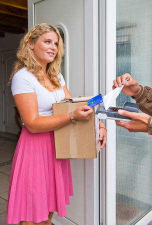 Young housewife accepting a cash on delivery package from a courier, paying with her debit card.