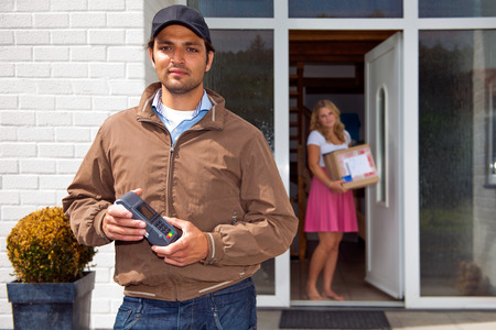 home delivery: Delivery guy, holding a wireless pin machine walking away from a house, where a woman stands in the doorway, with the just delivered parcel in her hand