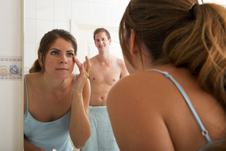 bending forward: Beautiful woman putting make up on in front of the mirror with her boyfriend waiting in the background Stock Photo