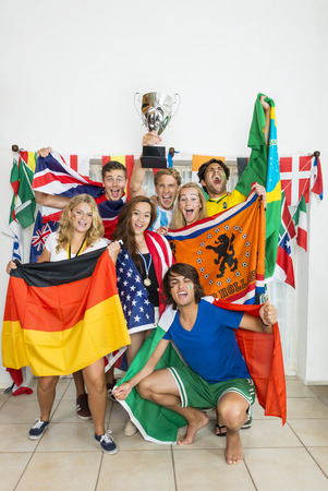 Portrait of successful athletes with various national flags celebrating at home photo
