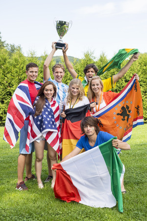 Portrait of successful athletes with various national flags celebrating in park photo