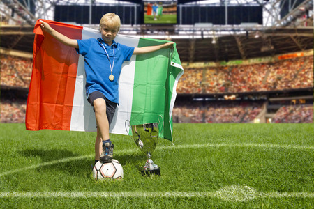 croud: Young child, proudly holding a large Italian flag stands like a champion in the center of a large soccer stadium