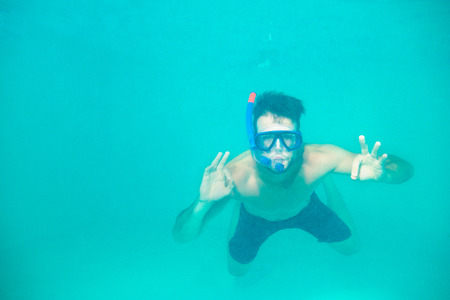 Portrait of a young man snorkeling in a blue clean water photo