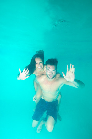 A young couple diving in a blue clean water and waving towards camera photo