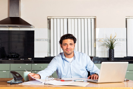 Handsome man doing his personal administration, such as taxes, paying bills and checking his finances at a kitchen table Stock Photo