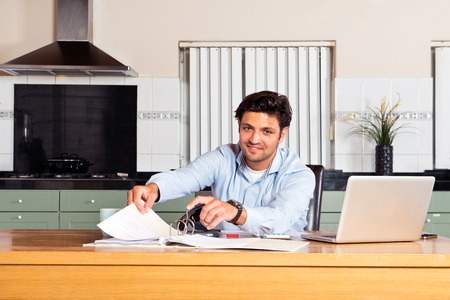 Handsome man filing paid giro cards and transaction forms in a binder whilst doing his personal administration getting his finances in order at the kitchen table
