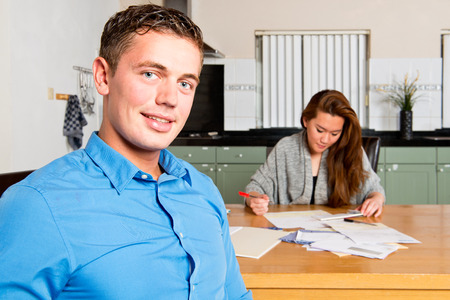 morgage: Young man sitting at the kitchen table, similng at the camera as she just finished getting her personal finances in order, with hus girlfriend still going through the paperwork, filing receipts, and signing giro transaction forms