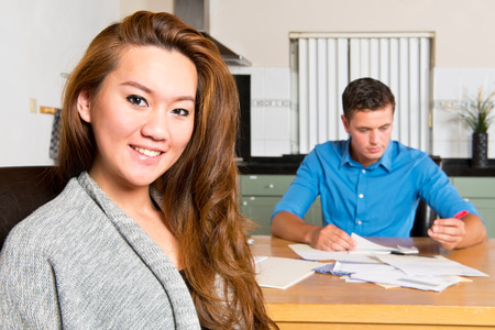 morgage: Young woman, sitting at the kitchen table, similng at the camera as she just finished getting her personal finances in order, with her boyfriend still going through the paperwork, filing receipts, and signing giro transaction forms Stock Photo