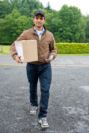 timely: Delivery guy bringing a cash on delivery parcel with online purchases to the door, with a wireless cash machine in his hand Stock Photo