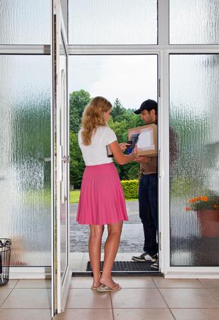 Frau accespts und zahlt für ein Paket, von einem männlichen Postangestellten vor ihrer Haustür geliefert