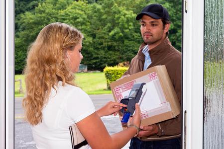 Junge Frau zahlt Ihre Nachnahmesendung zu einer Lieferung Postangestellten mit einem tragbaren, drahtlosen ATM