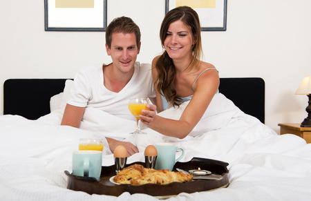 jus: young couple enjoying a rich breakfast in bed with croissants, fresh orange juice, boiled eggs and tea on a tray on a bright Sunday morning Stock Photo