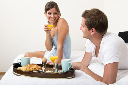 Young, pretty couple enjoying a luxurious breakfast in bed with croissants, tea, boiled eggs and fresh orange juice photo