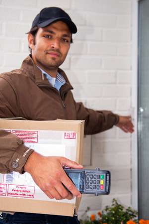 Postal worker, carrying a parcel and a portable ATM rings a doorbell with a cash on delivery service photo