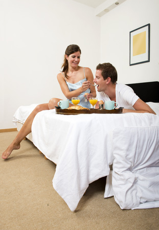 double bed: Pretty woman feeding her boyfriend breakfast in bed
