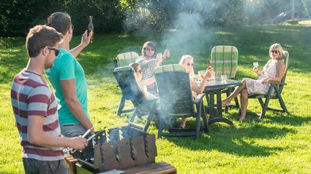 hombre tomando cerveza: Grupo de j�venes amigos disfrutando de la barbacoa en un jard�n en una tarde soleada