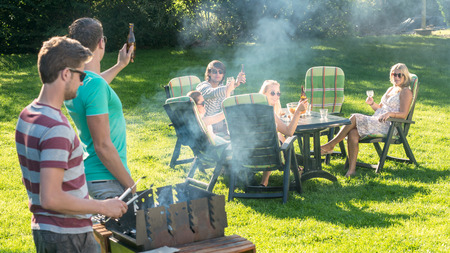 Group of young friends enjoying barbecue in a garden on a sunny afternoon