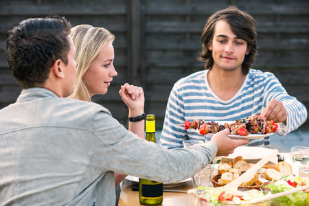 passing: Two young men and woman enjoying a dinner party outside Stock Photo