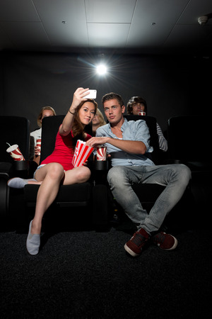 binge: A young couple watching a movie at a cinema and photographing themselves with a Smartphone