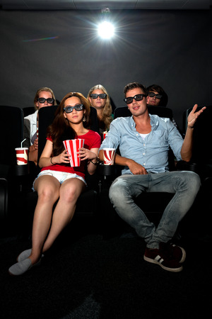 Group of young friends wearing 3D glasses watching a movie at a cinema photo