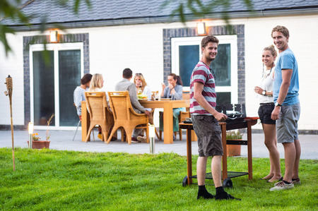 Groupe de jeunes amis qui préparent un barbecue dans une arrière-cour