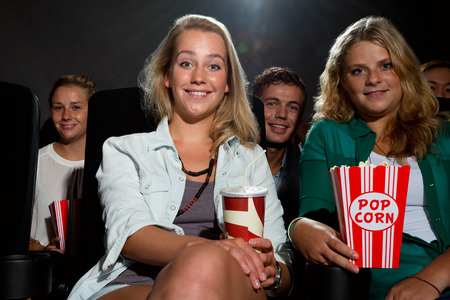 Group of young friends watching a movie at a cinema photo