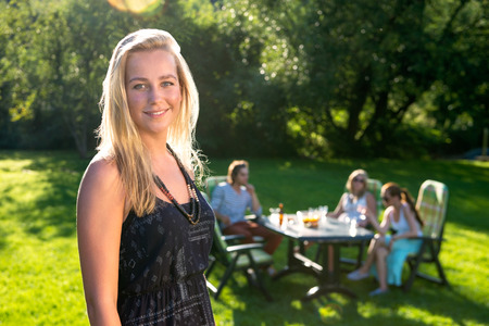 A young woman standing in a sunny garden while her friends enjoying a garden party in background photo