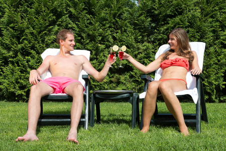 A young couple sunbathing in a back yard and toasting with tropical drinks
