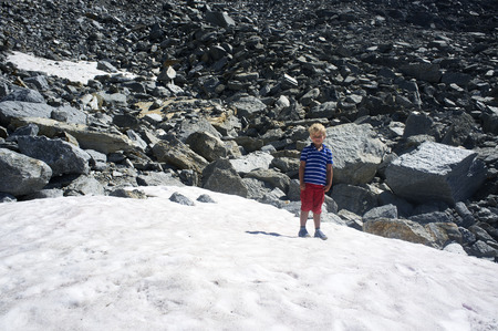 eroded: Young child standing on eternal snow in his shorts on a sunny summer day, surrounded by eroded rocks at high altitude in the Swiss Alps