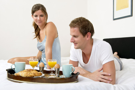 Cute couple enjoying a rich breakfast in bed, together, on a sunday morning photo