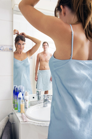 Man Looking At a Woman, Making her Hair in the reflection of a bathroom mirror, admiring her figure. photo