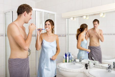 toiletries: Young Couple looks at eachother affectionately, whilst Brushing their Teeth In the Bathroom Stock Photo