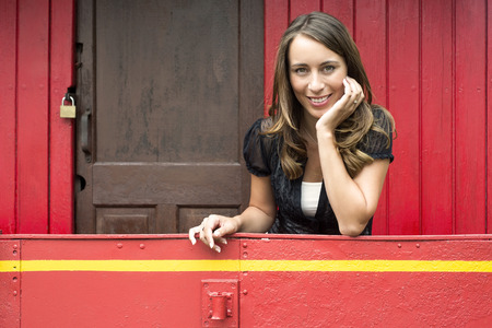 Portrait of happy young woman leaning on railing in red train caboose car Stock Photo - 22511311