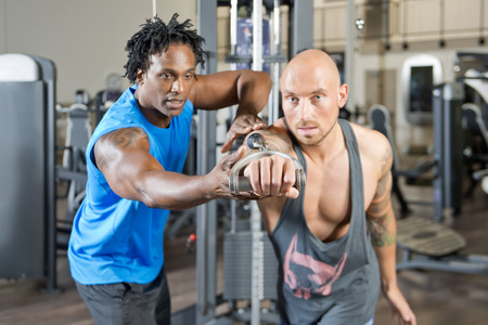 excersise: Personal fitness trainer giving instructions to a man, working out in a gym, focus on the hands Stock Photo