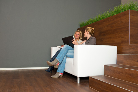 open office: Two, casually dressed, business women during an informal presentation, in discussion on a white leather couch in a modern open office space Stock Photo
